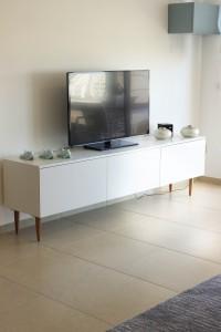 שידת טלויזיה מתכתבת עם שולחן הסלון. קלפה בגוון תכלת מעושן כתוספת אחסון גבוהה. עיצוב וצילום: רוית רוד