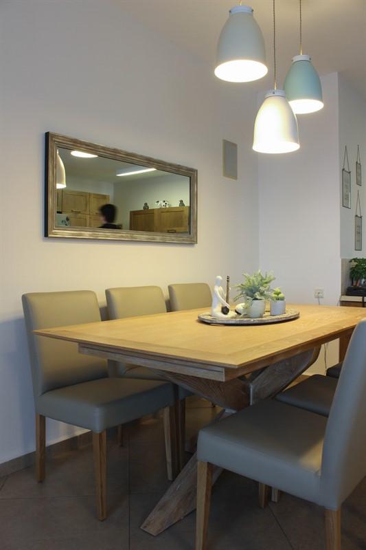 פינת האוכל. שולחן אלון מולבן, כסאות בריפוד בגוון טבעי וגוף תאורה בגוונים פסטליים.