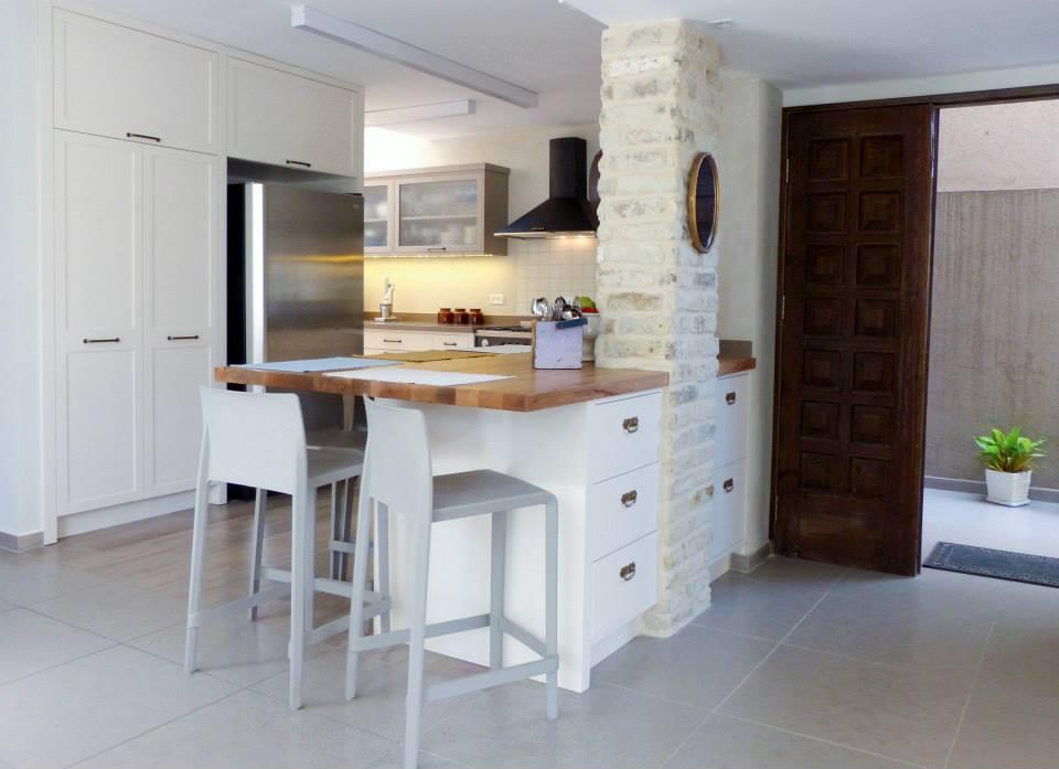 מבט אל הכניסה והמטבח אחרי. דלת הכניסה חודשה והוזזה כלפי חוץ בכדי לאפשר מקומות אחסון נוספים וארונות קיר מימין. עיצוב וצילום: תמי אקהאוס ורוית רוד