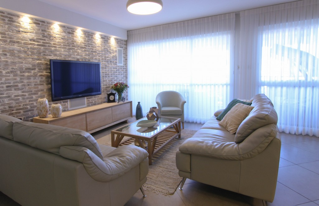 הסלון אחרי. גוונים רכים ועדינים, טקסטיל, וילונות ושטיח למראה הרמוני.