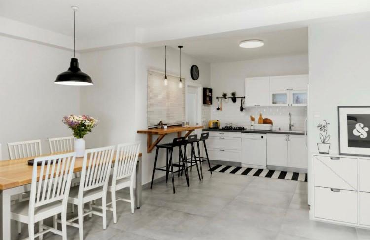 גוף תאורה צמוד תקרה במטבח, שני גופים עדינים מעל הדלפק ואחד דומיננטי מעל שולחן האוכל. מבלי להעמיס. עיצוב: רוית רוד צילום: מאיה חבקין