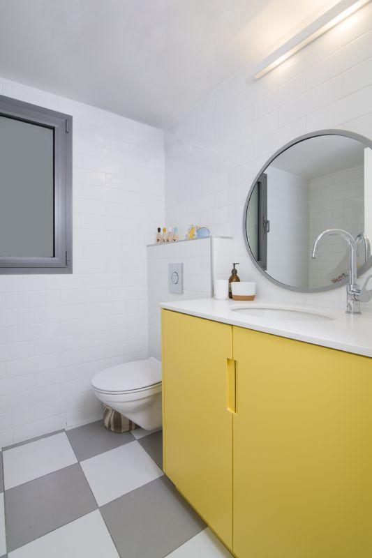 ארון צהוב וריצוף אפור לבן באמבטיית ילדים. עיצוב: רוית רוד צילום: עידן גור
