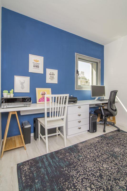 חדר העבודה בכחול כהה. השולחם הגדול שתוכנן בנגרות מכיל את כל הצרכים. עיצוב וצילום: רוית רוד