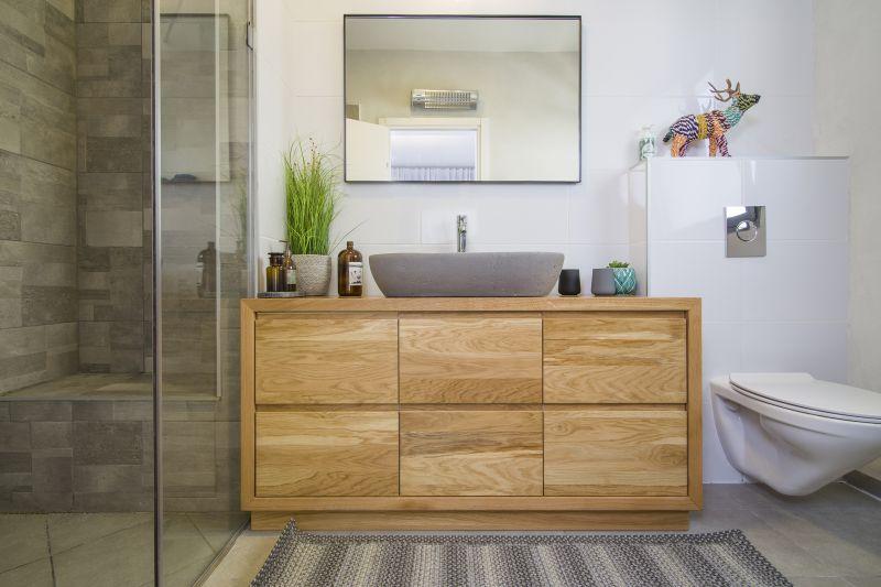 במלוא הדרו -חדר מקלחת הורים בגווני אפור בטון ובשילוב נגרות מעץ אלון. עיצוב וצילום: רוית רוד צילום: עידן גור